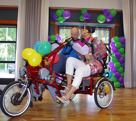 De heer Borsboom en Jose van Vliet rijden de fiets de feestzaal in